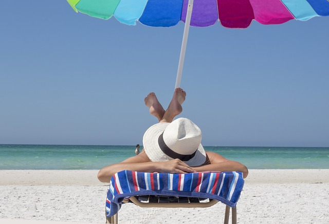 A lady simply sunbathing on a beach lounger by the beach on a striped towel