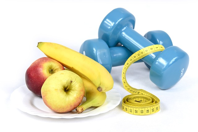 Blue hand weights with a tape measure draped over them next to a plate of apples and bananas